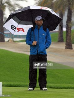 News Photo : Sergio Garcia of Spain shelters under his...