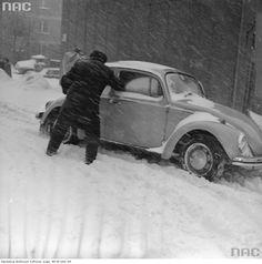 Mężczyzna odśnieżający samochód Volkswagen Garbus.