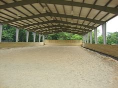 Protect your existing outdoor ring with similar roof canopy.  Any steel building can be built with no walls, partial walls or completely enclosed.