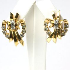 Bows of diamanté in gold-tone metal form these 1940s Retro Modern clip-back earrings by Mazer.