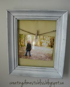 A tiny bit of twine glued to the back of the frame and a clothespin to hang an easily changeable photo :)