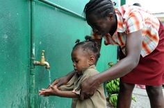 Marcia Gordon, a teacher at the UNICEF-supported Denham Town Basic School in the Denham Town community in the parish of Kingston and St. Andrew in Jamaica, helps a boy wash his hands at an outdoor water point outside the school. Many poor families cannot afford pre-school fees, books or uniforms, so their children do not attend school regularly. © UNICEF/Susan Markisz http://www.unicef.org