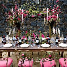 Another tablescape features similar but more wild-looking arrangements of cherry blossoms, cyclamens, hyacinth, tulips, ranunculuses, proteas, and ti leaves atop tall candelabras. Below, an arrangement of moss and stems of hyacinths and ranunculuses in vintage bottles fills the space between the place settings.