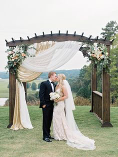 Bride and groom share a kiss under a rustic wedding arch: http://www.stylemepretty.com/2016/08/19/rustic-foxhall-resort-wedding/ Photography: Amy Arrington - http://www.amyarrington.com/
