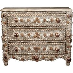 An incredible shell and mineral encrusted three drawer commode, reminiscent of Italian baroque grotto style. Pearlized natural shells create an overall lustrous, opalescent effect. The natural crystallized mineral accents add depth and texture. Large snail shells serve as pulls to the three fully functional drawers.This may be purchased on ecofirstart.com