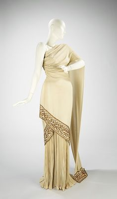 Beaded synthetic evening dress by Mme. Eta Hentz, American, spring/summer 1944.   This elegant evening dress is a superb adaptation of a classical garment for modern-day dress. The upper portion of the dress resembles a Greek chlamys or a Roman palla, while the fluted skirt mimics the bottom half of a Roman stola.
