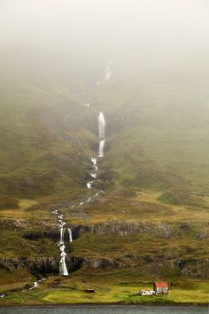 A nameless waterfall trickles beside a small house at the east coast in Iceland (by Kilian Schönberger on 500px)