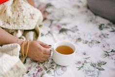 woman drinking green tea on her bed by Lia & Fahad| Stocksy United