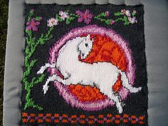 Knitted white horse. In the background is a celtic circle and some flowers.