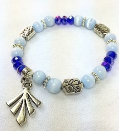 """This design Blue and White Bracelet, is made with blue and white 8mm Czech beads and silver connectors and a charm. The bracelets are made the size of a 7 1/2"""" bracelet."""