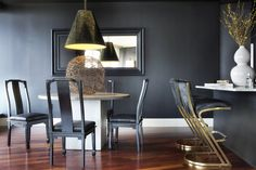 Black walls and a round white table in a dramatic dining space.