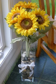 an arrangement for our sunroom - Dana used a tall square vase with large rocks, faux sunflowers  a wider white ribbon