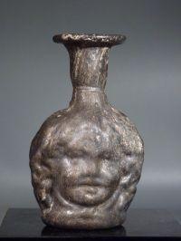 Roman molded purple glass Janus Medusa head flask.   2nd-3rd century AD   H. 7.8 cm (3 1/8 in.)   Intact. Fine black patina.
