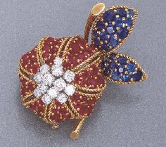 A RUBY, SAPPHIRE AND DIAMOND CLIP BROOCH Designed as a circular-cut ruby slightly bombé-shaped flower with circular-cut diamond cluster centre to the circular-cut sapphire petal and polished gold stem, mounted in 18k gold and platinum