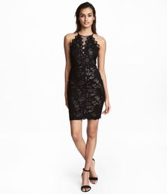 Black. Short, fitted dress in lace. Narrow-cut at top with narrow shoulder straps and button at back of neck. Low-cut opening at back, seam at waist, and