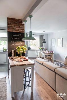 Sala de estar e jantar integrados com cozinha e bancada para refeições rápidas tipo carrinho.