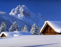 Snowy cabins with mountain backdrop.