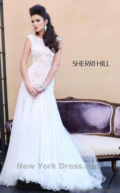 Sherri Hill 2981  Lacey Drop Waist Cap Sleeve Dress by Sherri Hill    Look amazing on your big day in this decadent evening dress from Sherri Hill 2981. The high neckline bodice has demure cap sleeves and is fitted in glamorous lace to the low hip. The full-length skirt floats to the floor in chic, wire-hemmed layers for an elegant look that sparkles and shines in every light
