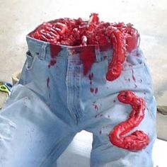 """It looks like you stuff the pants with newspaper to hold them up. Get the """"Great Stuff"""" spray foam for the hardware store. Spray on top of paper and the paint with red paint for blood look...."""