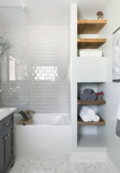 Bathroom, white subway tile, mosaic floor tile, glass shower tub, wood shelving | Carriage Lane Design-Build Inc.