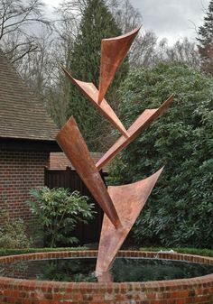 "Giles Rayner's Water Sculptures | Falling leaves - The 12-foot-tall sculpture contains five triangular ""leaves"" of reinforced copper. The water runs from the upper leaf, joining each torrent as it tumbles through the other leaves into the water basin. TARC TECHNOLOGY REVIEW"