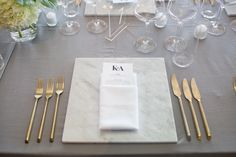 Grey table cloth with faux marble paper placemat, white napkin, purple menu and sprig of baby's breath