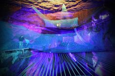 At Llechwedd Slate Caverns in Wales, brave souls will soon bounce through a cave on three ginormous trampolines. The huge springboards hang from the walls of a slate cavern -- the highest dangles a frightening 180 feet above the cavern floor. They're bathed in neon light, like an electric underground outer space.