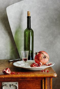 Green Bottle And Pomegranate - Still life with a green bottle of red wine and ripened pomegranates on wooden table with gray wallpaper on the background  by Nikolay Panov http://pixels.com/products/green-bottle-and-pomegranate-nikolay-panov-art-print.html