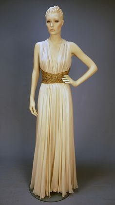 "RICHILENE BEADED CHIFFON HALTER GOWN, c. 1970. Cream silk, the bodice front and back gathered into a wide waistband of nude net covered in gold metallic embroidery, crystal beads and prong set aurora borealis paste jewels, full skirt having two layers of chiffon over satin under skirt, back zipper, neck hooks & eyes. Label ""Richilene New York."""