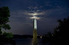 The supermoon lurks around clouds behind the small replica of the Washington Monument on the shore of Old Town Alexandria.