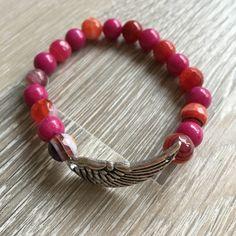 Armband van 8mm meerkleurig (roze/paars) agaat en fucsia roze jade, met metalen vleugel. Van JuudsBoetiek, te bestellen op www.juudsboetiek.nl