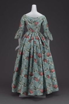 "Spitalfields brocade dress; dated ""mid-19th century, about 1840;"" United States. MFA # 53.192. ""Fabric 18th century Spitalfields brocade, blue ground, horizontal interlacing ribbon and floral serpentines, brocaded with white and brilliant polychrome silks, tightly fitted bodice coming to V in center front, hooked down center back, wide flaring neckline, elbow length sleeves with sleeve ruffles shaped like those of the 18th century, full skirt with fullness gathered evenly all around."""