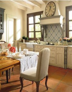 White kitchen with beautiful grays, natural wood, and terracotta tile floor.
