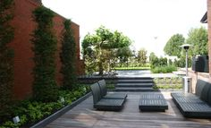 12 Landscaped Patios: Rodenburg Tuinencreate magnificent plant-filled areas, as well as interesting hardscapes. Here, vertical plantings soften an expanse of brick, while terraced trenches line up with the stairs.
