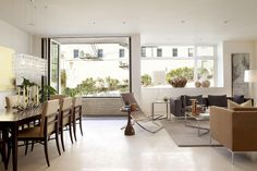 Sala de estar com piso branco, tapete cinza, poltronas marrom, mesa de jantar de 8 lugares, mesa de centro. Decoração Contemporânea em São Francisco  porJohn ManiscalcoArchitecture