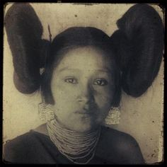This is an image is of a Hopi woman taken in 1901. She wears turquoise mosaic earrings, a necklace of glass seed beads and a traditional black manta. Her butterfly hairstyle is a typical hairstyle of women who were ready for marriage but not yet married.