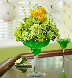 Toast that special occasion in style -- send our truly original lime margarita arrangement. Mixed with yellow roses, green carnations, green spider mums, poms and hypericum, this fresh floral cocktail is hand-arranged in an oversized acrylic margarita glass. Accented with realistic green lime slices and green straws, it's an unforgettable gift that will keep the party going.