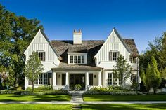Board and batten siding, white brick, arts and crafts style tapered columns, and a shed dormer.
