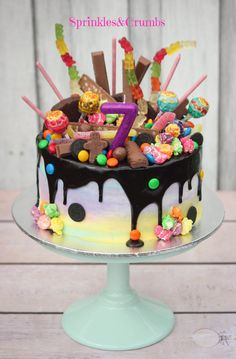 Rainbow candy drip cake pale frosting paired with crazy toppings. Awesome combo