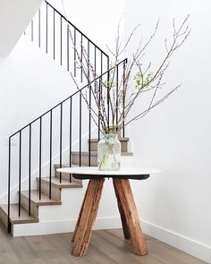 Entryway: decorative branches in glass vase on white marble-top table with wooden legs; solid timber floorboards and staircase; black metal balustrade