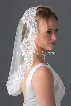 A traditionally styled short mantilla veil with flowery wide lace. This veil lays flat on the comb with no gather. The lace is 4.5 inches wide. The veil is 20 inches long and 54 inches wide, on a thre