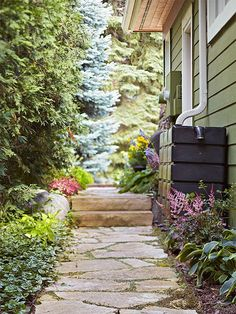 Create an inviting bridge between front and back with a well-landscaped limestone path. On the right, rain barrels put the oft-overlooked space to work.