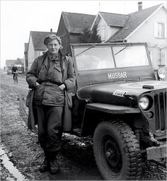 British Vogue photographer Lee Miller smiles in combat fatigues in Alsace 1944. It was said that no soldier could resist a photographer with a fashion model's striking beauty