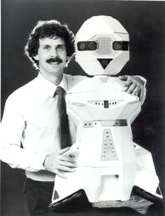 Tom Frisina with a TOPO model personal robot, 1983. The robot was designed by Androbot Inc. to perform every day tasks around the house. TOPO did not contain an internal microprocessor and could receive commands through an external PC such as an Apple II. TOPO retailed for $795 and sold approximately 1,000 copies before it was replaced by the BOB in 1984.