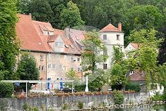 Photo made in the town of Landsberg am Lech in Bavaria (Germany). In the photo, it made from the bridge over the river Lech, seen on the river bank some roofed houses very pendendi characteristics of the region and a tower surrounded by green trees. The houses are full of windows with white serranenti.