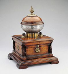 A LARGE TABLE TOP COFFEE MILL, France, 18th c. Walnut carved with acanthus leaves and brass.