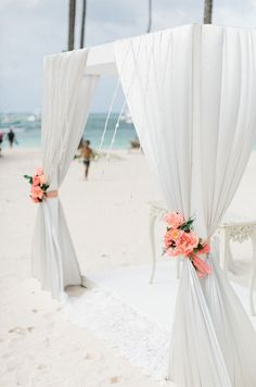 Bright coral flowers pop against the crisp white linens on this ocean side altar.