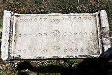 """Ludus duodecim scriptorum, or XII scripta, was a board game popular during the time of the Roman Empire. The name translates as """"game of twelve markings"""", probably referring to the three rows of 12 markings each found on most surviving boards. The game tabula is thought to be a descendant of this game, and both are similar to modern backgammon."""