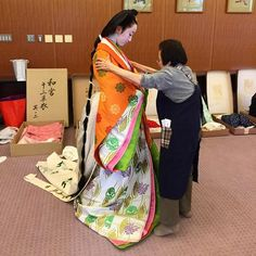 A woman being dressed in junihitoe