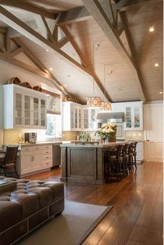Open Concept Kitchen. Cathedral ceiling, white glass cabinets, wood floors, stained kitchen island